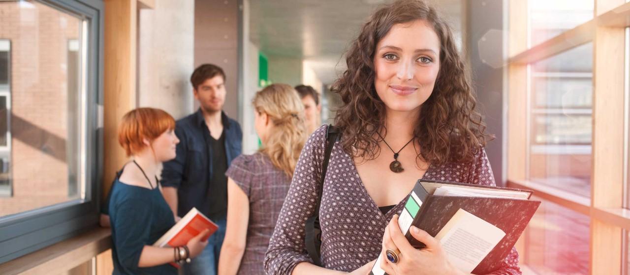 Studentin mit Akten auf dem Arm